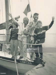 Welcome back; world sailors. Sailors Fiona McCall; Paul Howard and their children Penny and Peter acknowledge welcome-back greetings from boats and spectators at harbouriront yesterday after their five-year; round-the-world Voyage aboard their boat; Lorcha.